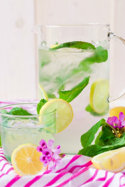 Iced mint lemonade in a pitcher and glass with fresh lemon slices and mint.