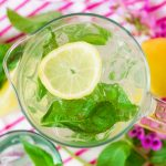 Mint lemonade over ice in a pitcher with fresh lemon slices and mint.