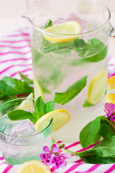Iced mint lemonade in a pitcher and glass with lemon slices and fresh mint.