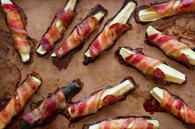 Bacon wrapped zucchini on a baking pan.