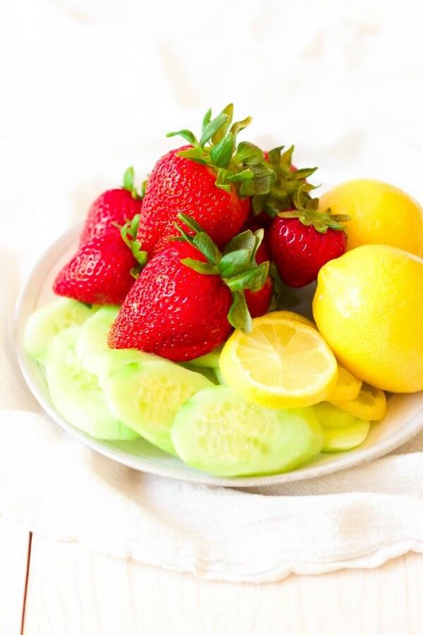 Plate full of fresh strawberries, lemons, lemon slices and cucumber slices.