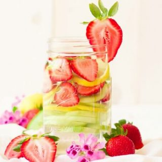 Mason jars filled with water, strawberries, lemon slices and cucumber slices.