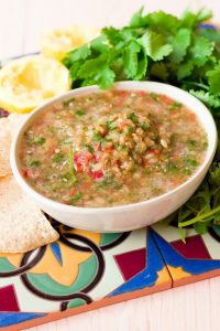 Large bowl of chunky blender salsa surrounded by chips, cilantro and juiced lemons.