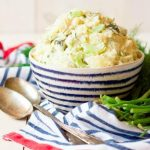 Bowl of potato salad surrounded by fresh dill.