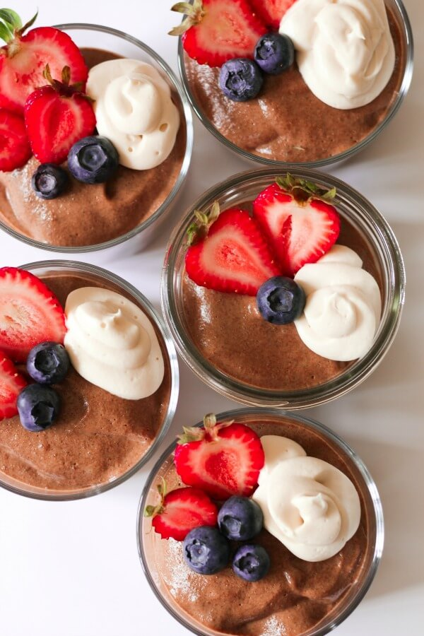 Jars of smooth chocolate chia pudding with fresh berries and cream on the top.