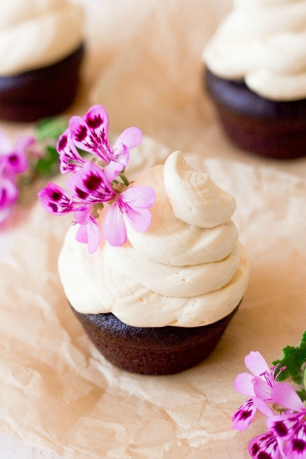 Vanilla buttercream frosting swirled on top of chocolate cupcakes with pink flowers.