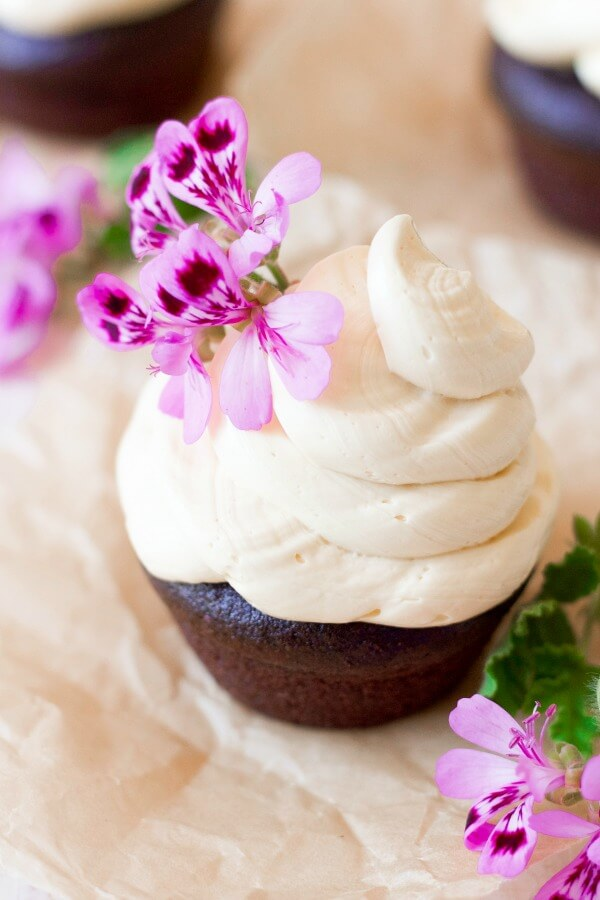 Vanilla buttercream frosting on top of chocolate cupcake with pink flowers.