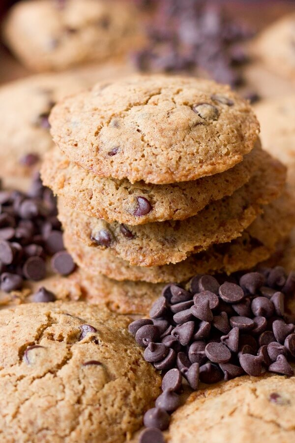 Stacks of chocolate chip cookies surrounded by chocolate chips.