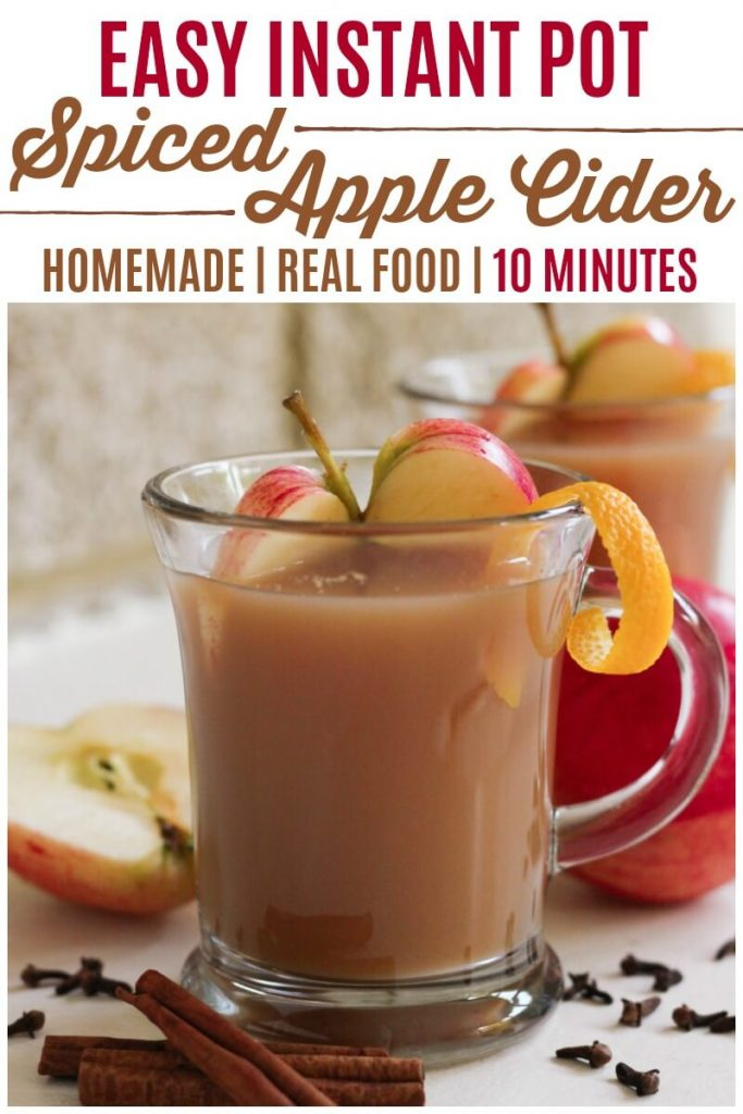 Glass mug full of apple cider, sliced apples and orange zest.