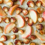 Roasted Brussels sprouts and apples on a baking sheet.