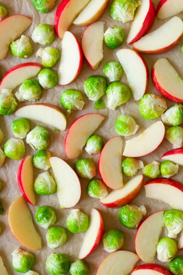 Brussels sprouts and apples on a baking sheet.