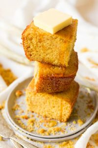 Stack of cornbread slices with butter and honey drizzle.