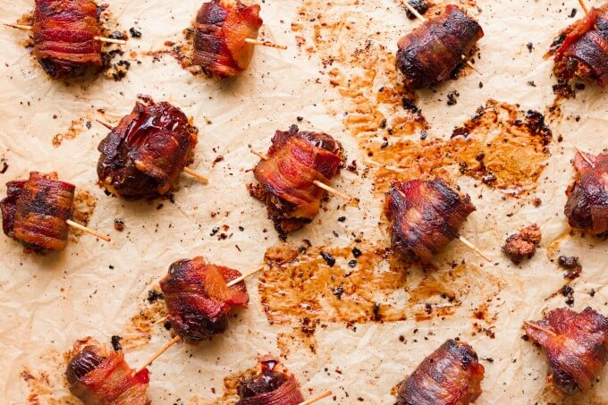 Bacon wrapped dates on baking sheet.
