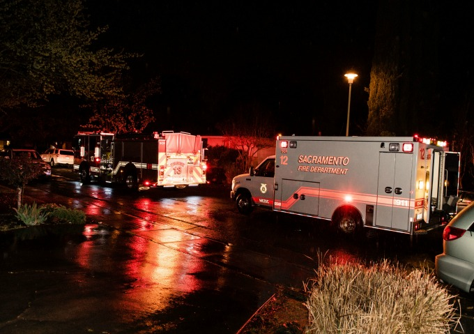 A firetruck and fire department ambulance with lights flashing on a rainy night.