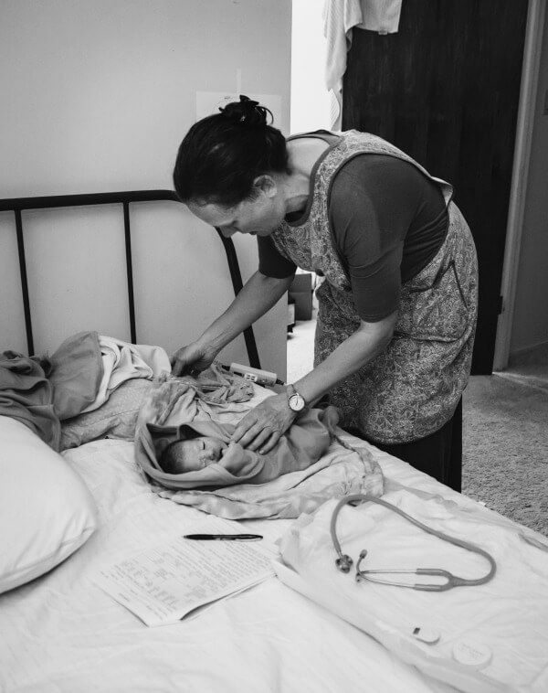 Newborn baby getting his newborn exam at home by his midwife after his home birth.