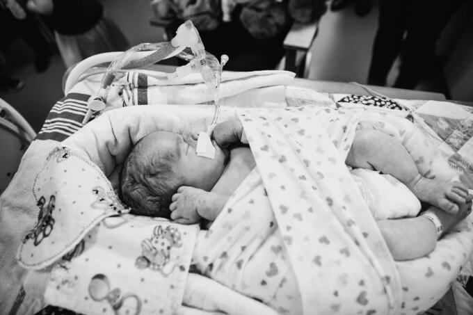 Newborn baby wrapped up in his bed in the NICU surrounded by family.